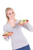 Choices: Woman Trying To Choose Between Burger and Healthy Wrap Stock Images