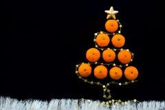 Choinka robić z pomarańczowymi mandarynkami i złotą gwiazdową girlandą przy czarnym tłem Obraz Stock