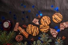 Choinka rozgałęzia się, ciastko gwiazd błękitni cynamonowi kije na czarnym rzemiennym tle z miejscem dla teksta fotografia royalty free