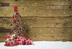 Choinka z czerwieni teraźniejszość i śnieg na drewnianym śnieżnym backgr
