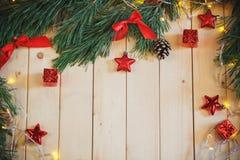 Choinki gałąź, czerwony łęk, prezenta pudełko i girlanda na świetle wo, Obraz Stock