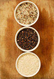 Choise of rice. Three different rice bowls on a wooden background Royalty Free Stock Photography