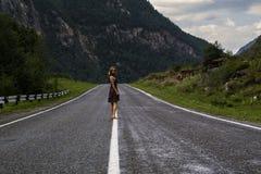 Choisissez la femme aux pieds nus marche le long de la route de montagne Voyage, tourisme et concept de personnes Image stock