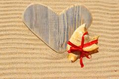 Choisissez le coeur et le coquillage en bois d'amour dans le sable Photos stock