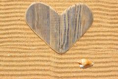 Choisissez le coeur et le coquillage en bois d'amour dans le sable Image stock