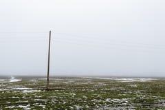 Choisissez le poteau électrique dans un domaine avec la neige en hiver Photographie stock