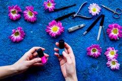 Choisissez le vernis à ongles pour la manucure Bouteille de prise de main de femme de poli sur la vue supérieure de fond bleu Photo libre de droits