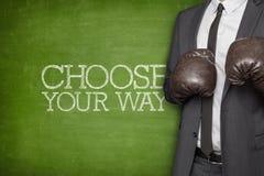 Choisissez votre manière sur le tableau noir avec l'homme d'affaires Image libre de droits