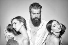 Choix difficile Homme barbu et deux femmes Photo libre de droits