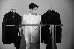 Choix difficile veste dans des mains de l'homme choisissant l'équipement, garde-robe, cintre de achat image stock