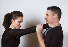 Choke Hold. A young woman choking a man with both hands around his throat stock image