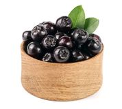 Chokeberry με το φύλλο στο ξύλινο κύπελλο που απομονώνεται στο άσπρο υπόβαθρο Μαύρα μούρα aronia Στοκ Φωτογραφία