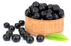 Chokeberry με το φύλλο στο ξύλινο κύπελλο που απομονώνεται στο άσπρο υπόβαθρο Μαύρο aronia Στοκ εικόνα με δικαίωμα ελεύθερης χρήσης