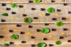 Chokeberry μούρων Aronia μαύρα, πέταλα calendula και φύλλα στο ξύλινο υπόβαθρο στο αγροτικό ύφος Στοκ εικόνα με δικαίωμα ελεύθερης χρήσης