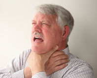 Choking man. A senior man with food stuck in his throat Stock Photos