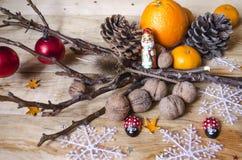 Choklad, citrusfrukter, muttrar med kottar och leksaker på bräden Royaltyfria Foton