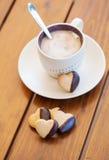 Choklad doppat hjärta format kakor och kaffe Arkivfoto