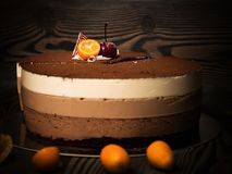 Choklad för kaka tre med garneringar på en mörk bakgrund Arkivbild