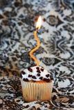 Choklad gå i flisor muffin med det orange stearinljuset Royaltyfria Bilder