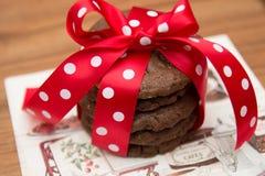 Choklad kaka med den pappers- servetten och röd siden- pilbåge med vita prickar Royaltyfri Fotografi