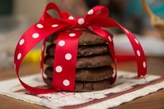 Choklad kaka med servetten och röd siden- pilbåge med vita prickar Royaltyfri Foto