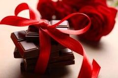 Choklad med det röda bandet och rosor arkivbilder