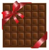 Choklad med ett rött band, bakgrund för en design Arkivfoton