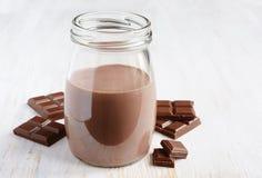 Choklad mjölkar med stycken av chokladstången royaltyfria bilder
