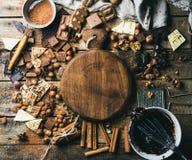 Choklad muttrar, kakaopulver, kryddor med träbrädet i mitt Arkivbild
