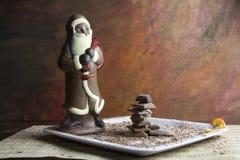 Choklad Santa Claus och chokladstycken på plattan Arkivbilder