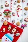 Choklad Santas, snögubben och kex near julstrumpan Arkivbilder
