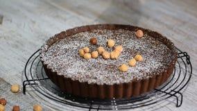 Choklad som är syrlig med hasselnöten på en platta på tabellen arkivfilmer