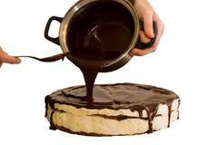 Choklad som flödar på kakan som isoleras på vit Arkivbilder