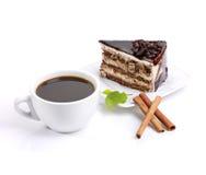 Chokladcake, kaffe och grön lövverk Arkivbilder
