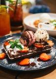 Chokladdillandetoppning med skopan av vanilj- och jordgubbeglass, piskar kräm, skivad jordgubbe Royaltyfri Bild