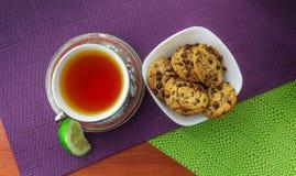 Choklade kakor med kopp te och citronen som beskådas från över royaltyfri bild