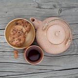 Choklade kakor med kopp te och porslinkokkärlet Arkivbilder