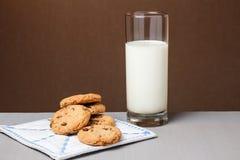 Choklade kakor och ett exponeringsglas av mjölkar på tabellen med brun bakgrund Royaltyfri Fotografi