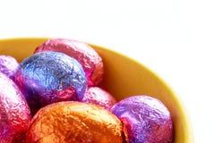 Chokladeaster ägg i gul bunke royaltyfria bilder