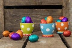Chokladeaster ägg i tre färgrika äggkoppar arkivfoton