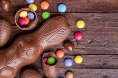 Chokladeaster ägg och sötsaker på träbakgrund arkivfoto