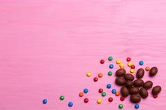 Chokladeaster ägg på en rosa bakgrund kulör godis och hjärtor Royaltyfria Foton