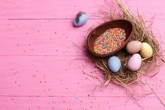Chokladeaster ägg på en rosa bakgrund kulör godis och hjärtor Arkivbild