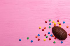 Chokladeaster ägg på en rosa bakgrund kulör godis och hjärtor Arkivbilder