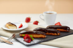 Chokladeclairs med nya jordgubbar på svart skiffer Eclairsefterrätt med bär och kaffe på vit bakgrund Royaltyfria Bilder