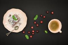 Chokladefterrätt, kopp kaffe och ny tranbär över svart bakgrund Top beskådar Royaltyfria Bilder