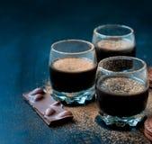 Chokladefterrättkoppar och chokladkakor som strilas med cocoen Arkivfoto