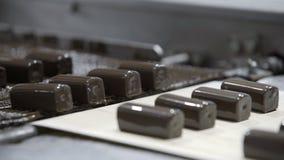 Choklader f?r produktionslinje f?r tillverkning av Godis som t?ckas med choklad S?tsaker fortskrider transport?ren arkivfilmer