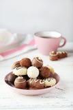 Choklader i bunke på den vita träbakgrunden Arkivbilder