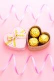 Choklader i en hjärta formade gåvaasken med det lockiga bandet Arkivfoto